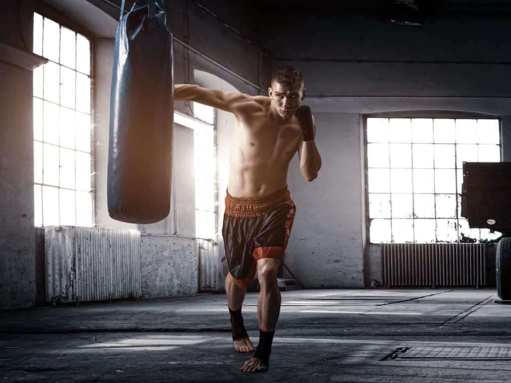 hombre golpeando un saco de boxeo